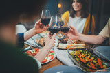 Happy friends enjoying healthy food drinking red wine and making cheers at home, Group of people celebrating together in cozy atmosphere, Dinner Family Friendship Holidays Concept - 245164183