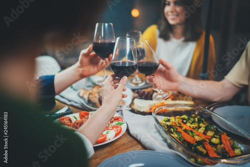 Happy friends enjoying healthy food drinking red wine and making cheers at home, Group of people celebrating together in cozy atmosphere, Dinner Family Friendship Holidays Concept