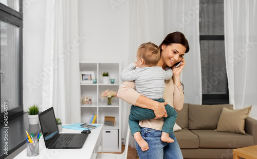 Leinwandbild Motiv motherhood, multi-tasking, family and technology concept - happy mother with baby calling on smartphone at home