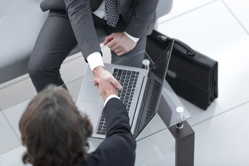handshake of business partners above the Desk.