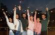 Leinwandbild Motiv leisure, celebration and people concept - happy friends with sparklers at rooftop party at night