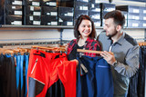 Young couple choosing touristic trousers in sports clothes store - 245172336