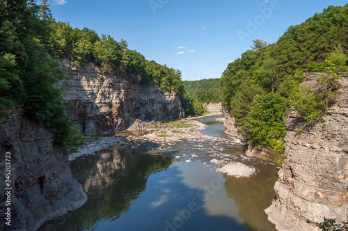 Foto Murales The Slow Moving Calm Waters of Summer on the Genesee River in New York's Letchworth State Park