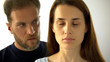 Man standing behind wife, sad lady with closed eyes hearing husband decisions