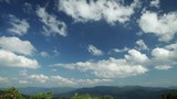 White clouds float on the blue summer sky. Below is a panorama of the mountain landscape. Time-Lapse Motion 4K video.