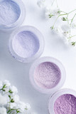flat lay jars of eye shadow in pastel spring colors on a white textured background with delicate white flowers gypsophila