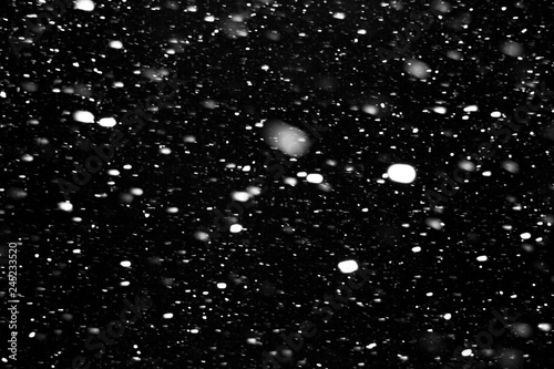falling snow on a black background, snowfall at night, white spots on a black background - 245233520