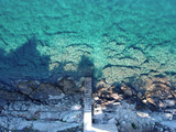 Beautiful beach of stones with stairs at fisherman town, Dalmatia, Croatia. Island Solta with crystal clean  water, south of Split, famous landmark and travel touristic destination in Europe.