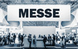 German text Messe, translate Trade Show. Crowd of people at a trade show booth with a banner and text