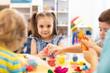 Leinwandbild Motiv Group of kids playing with modeling clay in nursery