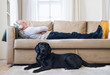 Leinwanddruck Bild - A happy senior man lying on a sofa indoors with a pet dog at home, listening to music.