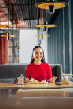 Cheerful beautiful woman with red lips eating breakfast in restaurant