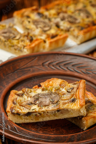 Homemade tart with mushrooms, leek, cheese and thyme on rustic background. Traditional snack cake. Lunch or dinner for gourmets. Selective focus - 245380181