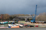 boat yard with storm approaching and railway bridge in background - 245403744