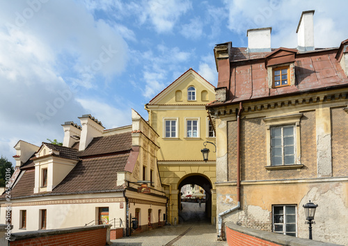 Fototapety, obrazy : Lublin is a city in eastern Poland. Old town with houses in the style of the Lublin Renaissance. Narrow streets, yellow lanterns, old colorful houses with interesting ornaments, pavement.