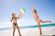 Two young girls in swimwear on summer beach vacation playing with ball