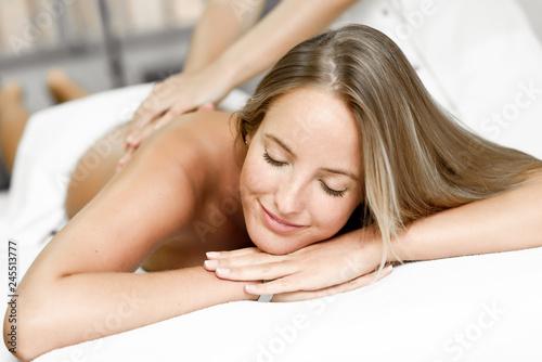 Leinwandbild Motiv Young blonde woman having massage and smiling in the spa