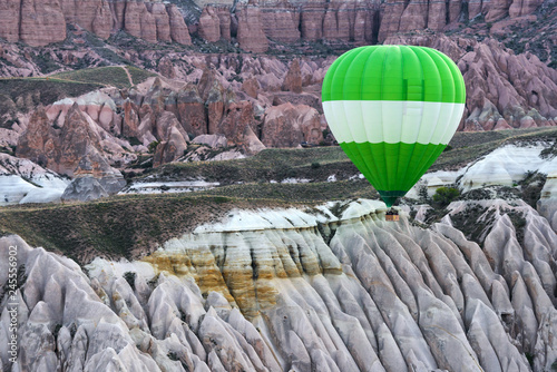 Green ballon in the sunrise mountains. Cappadocia, Turkey. Landscape photography - 245556902