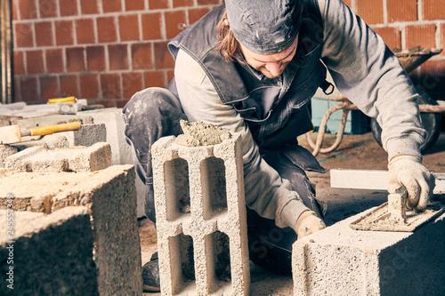 Leinwandbild Motiv Real construction worker bricklaying the wall indoors.
