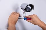 Technician Fixing Security Camera - 245564764