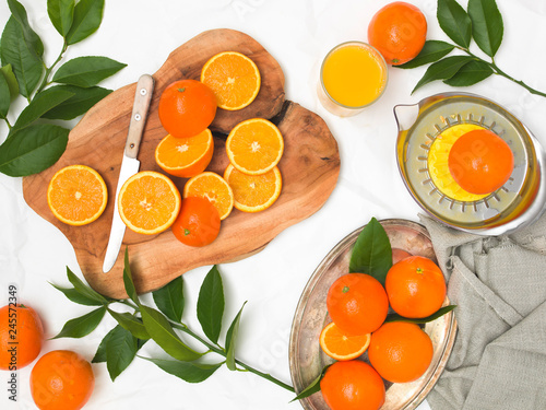 beautiful still life with oranges on white paper background and wooden board and knife