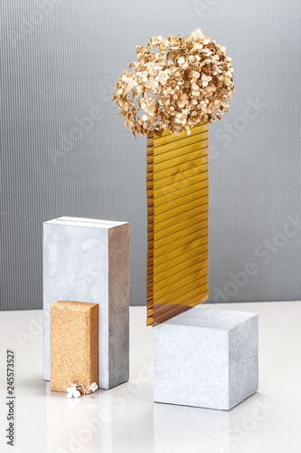 Still life using concrete blocks, textural building elements and a golden plant. © Tseytlin