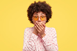 Stunned dark skinned woman with curly hair, covers both hands on mouth, afraids of something astonishing, dressed in fashionable shirt, isolated over yellow background, stands speechless indoor - 245584393