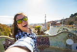 Travel and holidays concept - Young happy woman making selfie portrait with smartphone in Park Guell, Barcelona, Spain. - 245592917