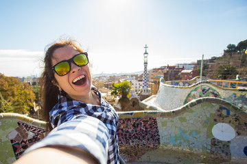 Travel and holidays concept - Young happy woman making selfie portrait with smartphone in Park Guell, Barcelona, Spain.