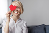 Smiling woman holding heart near eye
