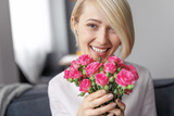 Cheerful woman with cute roses looking away
