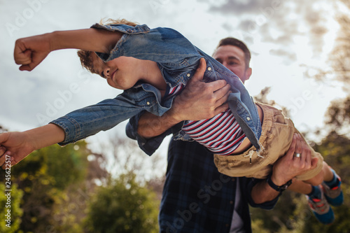 Leinwandbild Motiv Father and son having fun at the park