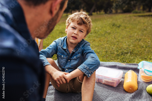 Leinwanddruck Bild Son having conversation with his dad at picnic