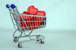 Valentines day concept. Miniature carts for store in which there are small plastic red heart on a white background.