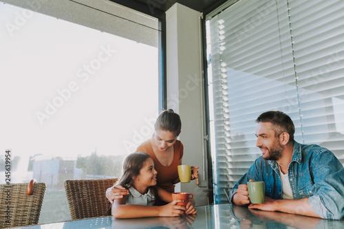 Leinwandbild Motiv Positive loving family drinking morning tea together