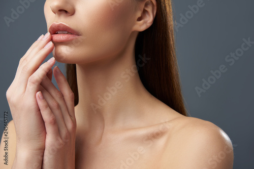 Young woman with beautiful full lips posing on blue-gray background