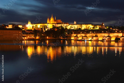 Prague, a beautiful night landscape with a view of the Charles Bridge, St. Vitus Cathedral, the reflection of lights in the water