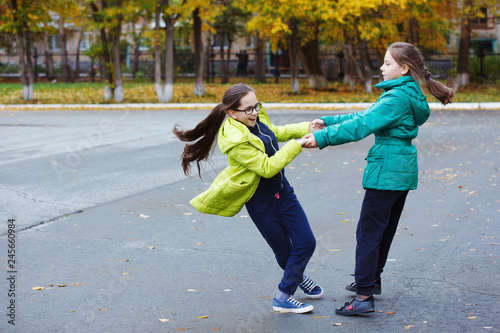 Two young pretty girls teenagers in yellow and green jackets play and have fun, dance in the autumn yard and pose for the photographer