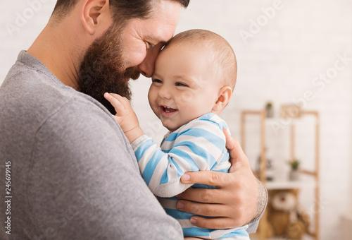 Leinwandbild Motiv Loving father embracing his cute baby son