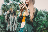 Young blond woman on vacation in the park searching information on smartphone. - 245701768