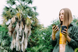 Young blond woman on vacation in the park searching information on smartphone. - 245702332
