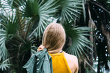 Young blond woman on vacation in front of coconut palm trees. Single traveler. - 245702515