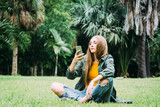 Young blond woman on vacation is sitting in the park searching information on smartphone. - 245702971