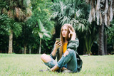 Young blond woman on vacation is sitting in the park searching information on smartphone. - 245703370