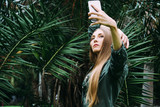 Young blond woman on vacation take picture with smartphone in the park. - 245703969