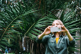 Young blond woman on vacation take picture with smartphone in the park. - 245704125