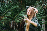 Young blond woman on vacation take picture with smartphone in the park. - 245704353
