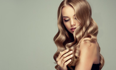 blonde girl with long  and   shiny wavy hair .  Beautiful  smiling woman model with curly hairstyle .  © Sofia Zhuravetc