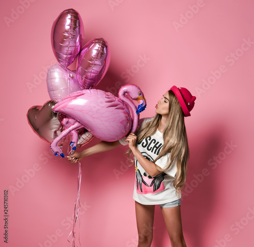 MOSCOW, RUSSIA, DECEMBER 2018 - Shapely girl in white t-shirt and cute hat holding colorful balloons for party  - 245710302