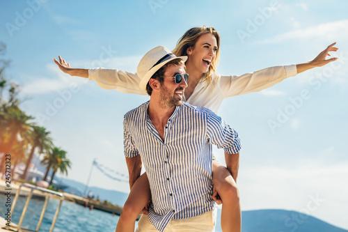 Leinwandbild Motiv Couple in love, enjoying the summer time by the sea.Joyful girl piggybacking on young boyfriend having fun.